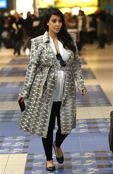 Kim kept her baby bump under wraps in a patterned wrap coat while stepping out in Paris on April 2, 2013