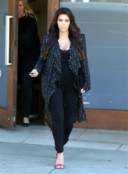 Kim wore a long wrap sweater over black leggings and a tee while shopping in Los Angeles on April 8, 2013.