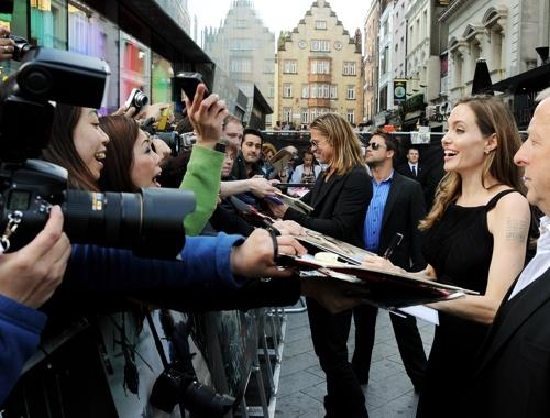 Jolie and Pitt sign autographs for fans.