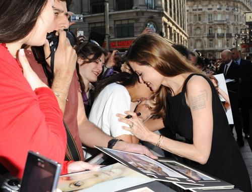 Jolie comforts a fan as she signs autographs