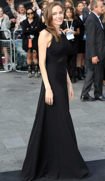 Jolie's long black gown brushed against the black carpet.